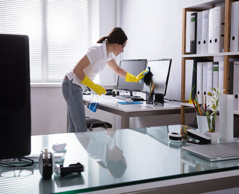 Being cautious while cleaning a worker's desk area.